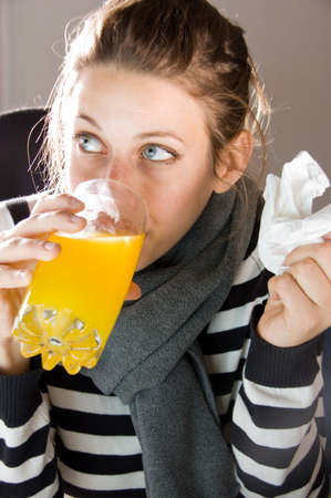 hayfever: Woman with the flue holding tissue while drinking orange juice Stock Photo