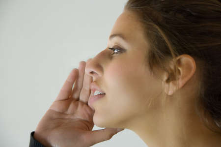 woman having a private conversation by holding her hand to her mouth. She could also be ready to shout. Stock Photo