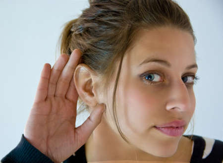 Young woman listens with her hand at right ear on white background.