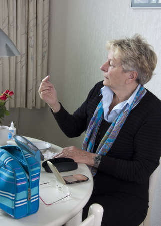 Senior woman is putting in her contact lenses at her table