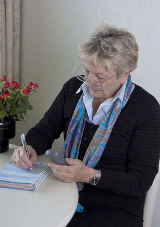 Senior people - woman is writing an entry in her agenda