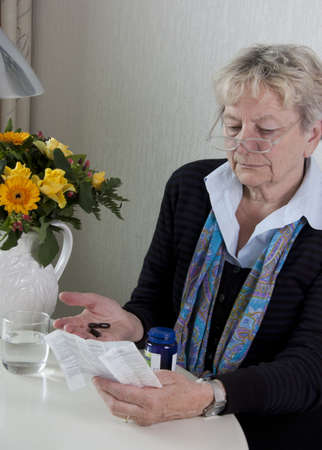 Health issues - senior woman is reading the instructions of her medication