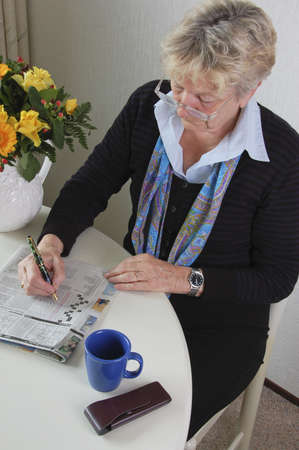Woman is doing the newspaper crossword puzzle during a coffeebreak