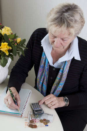 Woman is checking houshold money. Using a calculator