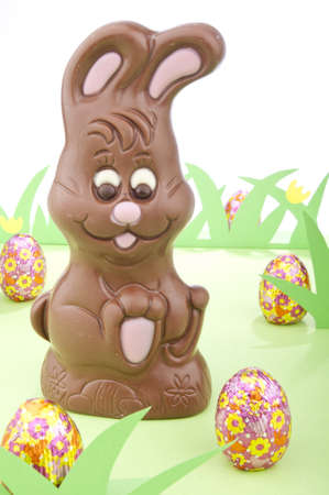 easter bunny made out chocolate surrounded with colored eggs in a field of grass. Stock Photo