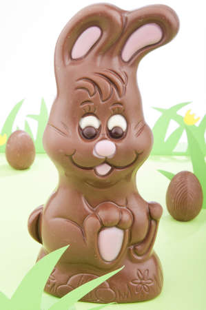 Easter bunny made out chocolate surrounded with chocolate eggs in a field of grass. Stock Photo