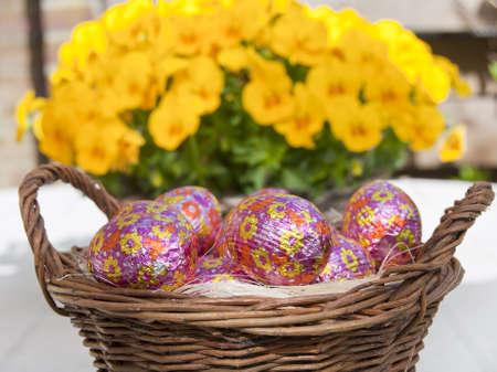 Basket of Easter eggs against a flower background.