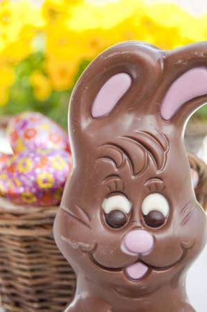 Chococolate Easter bunny in front of basket with Easter eggs. Stock Photo