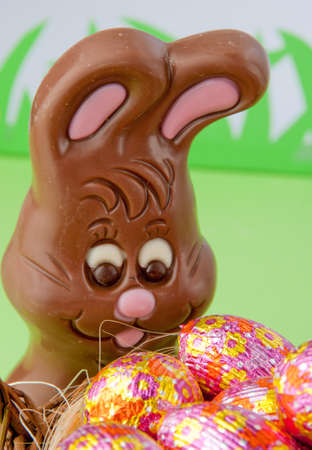 Chocolate Easter bunny behind a basket of decorated eggs