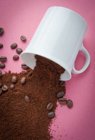cup with coffee grind and coffee beans spilled on a pink background photo