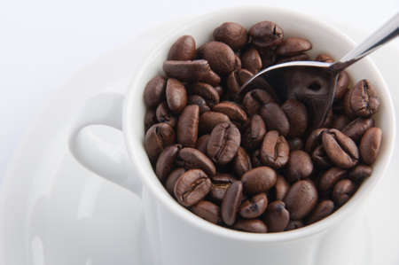 cup of coffee filled with coffeebeans and a silver spoon. Stock Photo