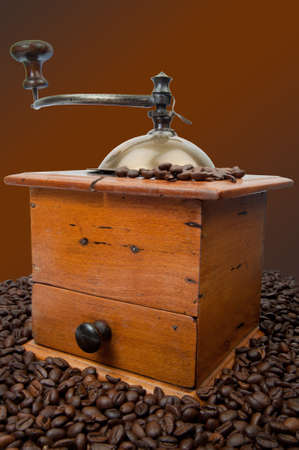 Old fashion coffee grinder against a white background with coffeebeans