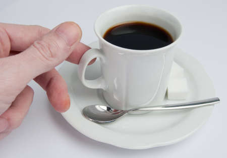 Hand moving the coffee cup into possition so it can be picked up