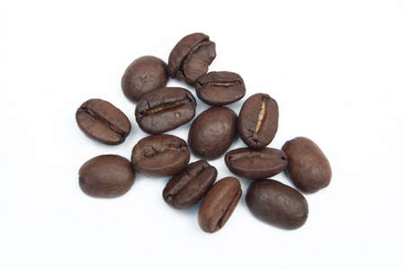 Closeup of isolated coffee beans against a white background.