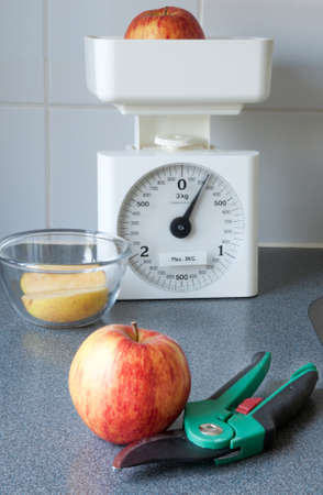 Apples and a scale on a kitchen counter. It looks like it is freshly cut from the apple tree. Stock Photo