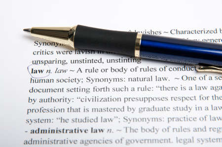 Translation of the word law in the dictionary with pen photo