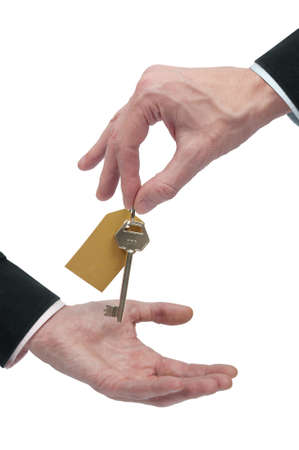 Two businessmen exchange the key to a real eastate property or the key to success.