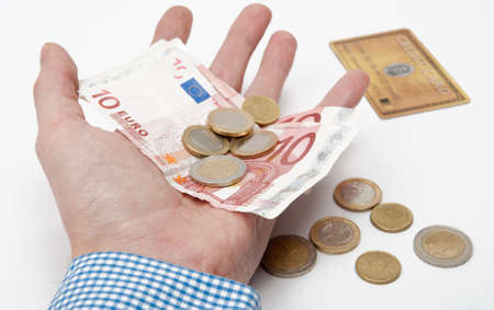 male hand holding several Euros in his hand. In the background there is a credit card.