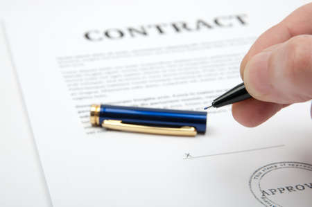 Hand holding a pen, ready to close the deal and sign the contract.