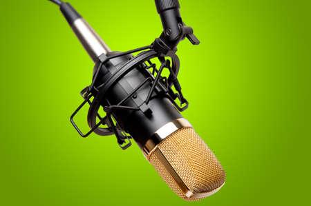 콘덴서 녹음 스튜디오 마이크의 근접 촬영입니다. 신선한 녹색 배경에 대해 촬영.