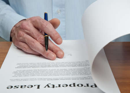 Male businessmen is reading the property lease contract before signing it