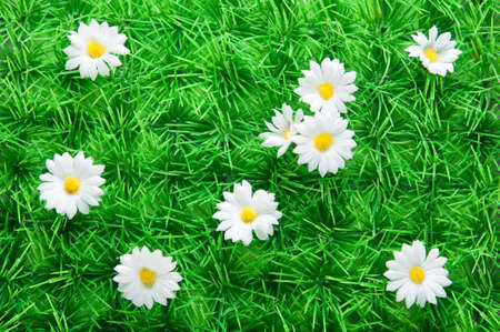 Artificial grass with Daisies made out of fabric.