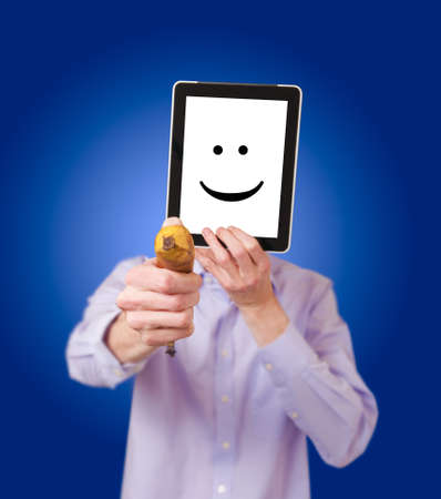 Anonymous robber with banana holding a tablet to cover his face against a blue background.