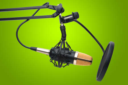 Condenser Microphone as used for radio and studio recording. Taken against fresh green background. Stock Photo