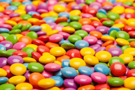 smarties: Large surface of multy colored candyviewed from the side.
