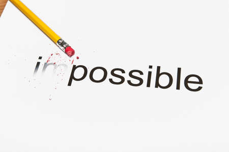Changing the word impossible to possible by erasing the first 2 characters. Stock Photo