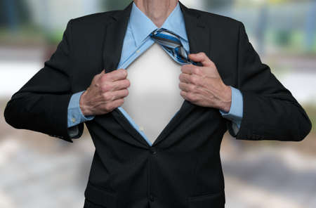 Businessman tearing his shirt and suite open with both hands. Showing the white shirt under it.