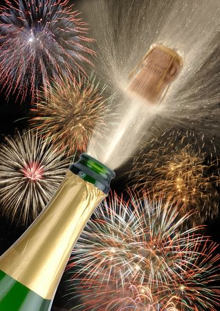 new years eve background: a bottle champagne is opened while a fireworks Stock Photo
