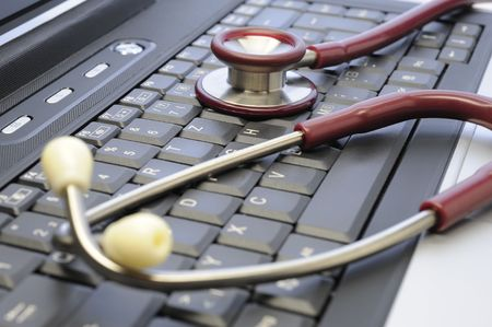 info business: medicine stethoscope on a computer keyboard