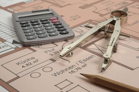 house building plan with compasses and hand calculator photo