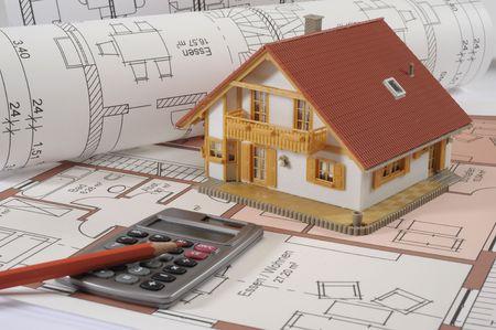 calculadora: Plan de construcci�n de viviendas con la calculadora a mano Foto de archivo