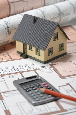 Model house and calculator on construction plan  Stock Photo