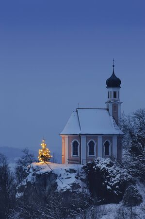 christmas chapel and illuminated tree at night photo