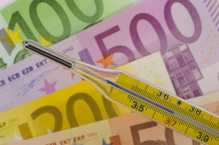 clinical thermometer and euro banknotes photo