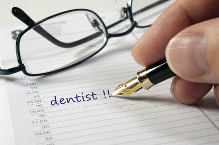 appointment: doctor dentist date written in calendar Stock Photo