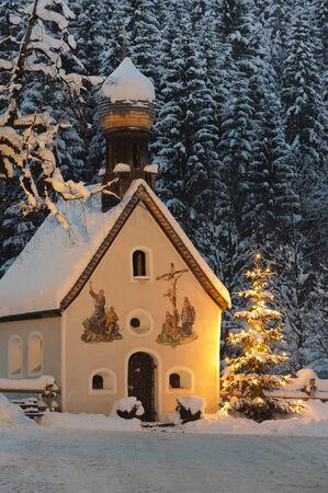 christmas chapel and illuminated tree at night photo
