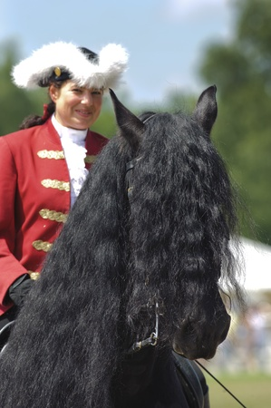 MUNICH, GERMANY - JUNE 4:  portrait of Friese horse with styled long mane and baroque rider while a public show at international equestrian challenge -Pferd International 2011- at June 4, 2011 in Munich, Germany