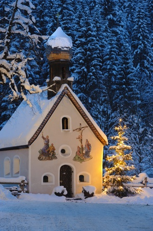 christmas chapel at evening with illuminated tree photo