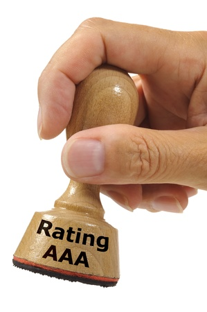 rubber stamp in hand marked with financial rating AAA photo