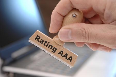 timbro di gomma in mano contrassegnati con rating AAA finanziari Archivio Fotografico