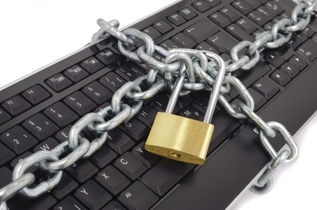 lock and chain: locked chain on computer keyboard as sybol for danger in internet Stock Photo