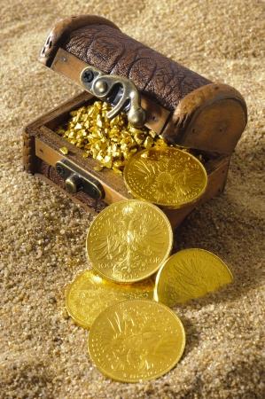 schatkist met gouden munten aan het zandstrand van Stockfoto