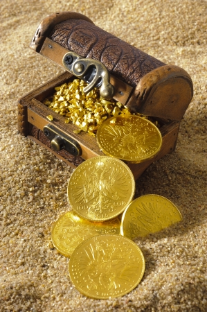 treasure chest with gold coins on sandy beach photo