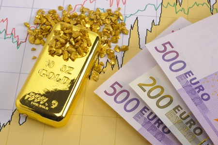 gold bar, nuggets and euro banknotes on financial chart photo