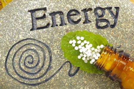 glóbulos homeopáticos en la piedra de la energía Foto de archivo