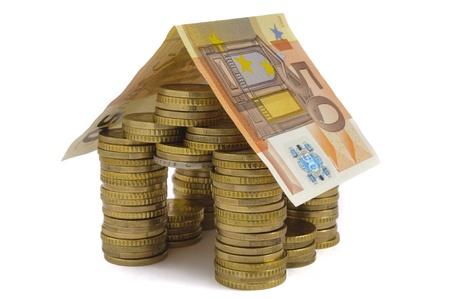 casa costruita con i soldi monete isolato su sfondo bianco